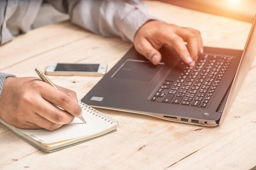 a picture with a laptop and the hands of a man, his left habd on the keyboard while the right hand is holding a pen and taking notes on a notebook and an iphone between the arms and in the space between his chest and the laptop sitting on the desk