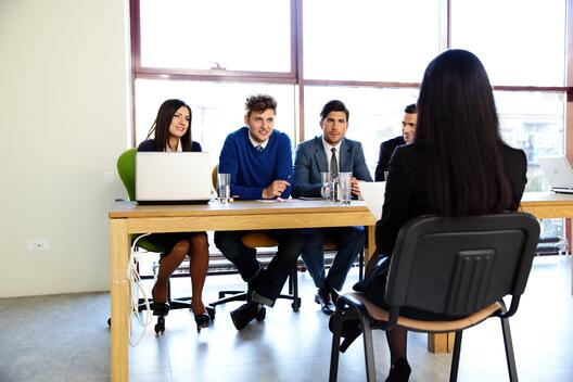 4 people sitting next to eachother on a table sitting in front of a woman with black hair sitting in a foldable chair with her back towards as and they 4 people looking to be in an interview
