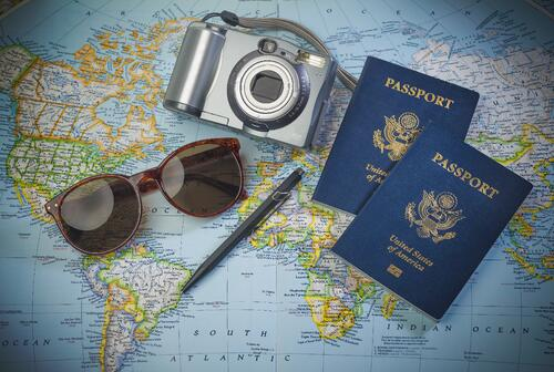 picture of a map, a camera, and passport to signify the action of travelling