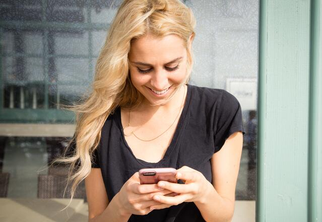 image of a woman of blonde hair looking down on her phone, which she is holding with both hands, while smiling.
