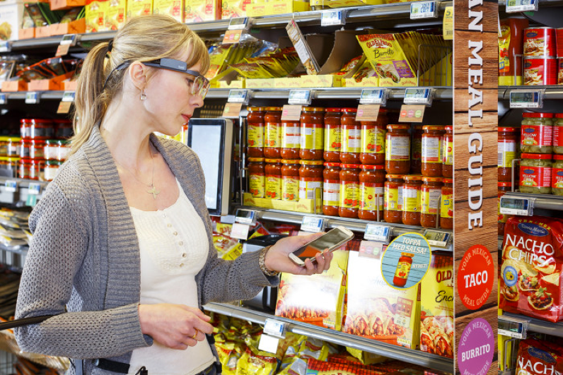 a blonde woman wearing hololens, while holding a celphone at a grocery store