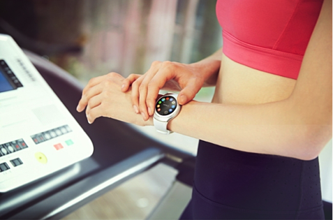Image of a girl at the gym tuning her smart watch