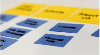 blue and yellow sticky notes on a white paper for card sorting